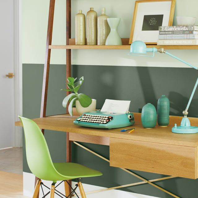 A two-tone green home office wall with green office chair